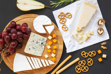 Tasting various types of cheese with fruits, walnuts, pretzels and bread sticks on dark background. Food for wine, romantic. Flat lay. From above, top view.