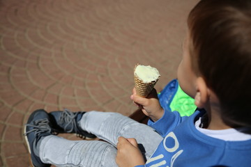 waffle ice cream in a child's hand close-up. the child takes a bite of ice cream