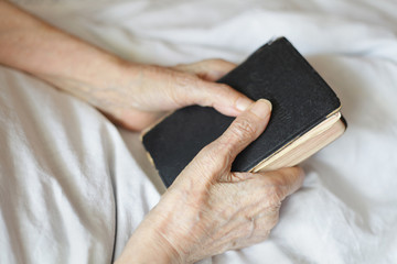 Hands of a senior woman on cane. Senior lying in a bed.
