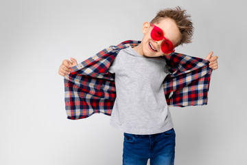 A handsome boy in a plaid shirt, gray shirt and jeans stands on a gray background. A boy in red sunglasses. The boy pulls his shirt back.