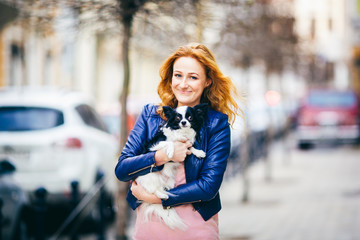 Subject man and dog. young red-haired Caucasian woman with freckles on face holds black and white shaggy chihuahua breed dog. The girl dressed in blue leather jacket, stands on busy street in spring