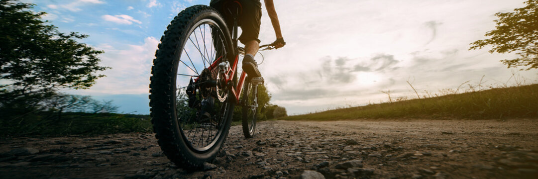 Young man traveling riding bicycle along a country road in sunset light. Bicycle sports, healthy lifestyle and activity