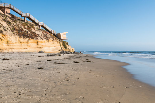 A view of Solana Beach, California, facing south toward Del Mar, with beach access steps and lifeguard station.
