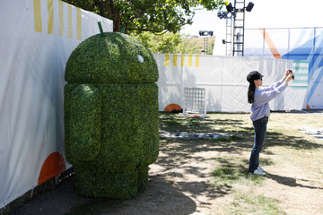 An attendee takes a photo with a Google Android mascot during the annual Google I/O developers conference in Mountain View, California