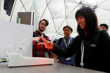 An attendee competes in a game of rock, paper, scissors against a Handbot robot during the annual Google I/O developers conference in Mountain View, California