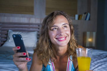 young attractive and beautiful woman at home in bed using internet social media app on mobile phone smiling happy drinking healthy orange juice relaxed