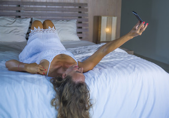 young attractive and beautiful woman at home in bed using internet social media app on mobile phone smiling happy