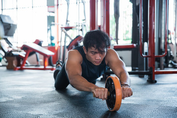 Front view man using abdominal roller