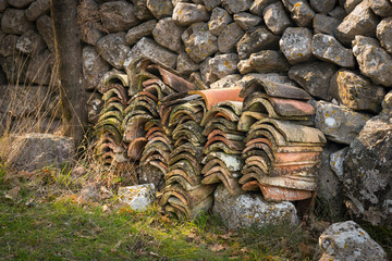 A pile of roofing tiles lying in front of a stone wall
