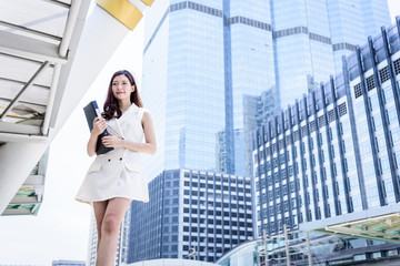 The asian business woman working and operation in outside office with building and city background.