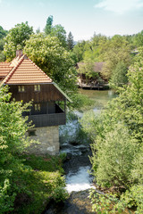 Village of Rastoke by a Korana river with wooden houses and a waterfall, Croatia