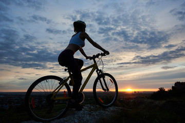 Side view of young lady cycling with an evening landscape. Girl in helmet enjoys sunset on the top of mountain against backdrop of city in distance under fairytale sky with clouds and bright sun