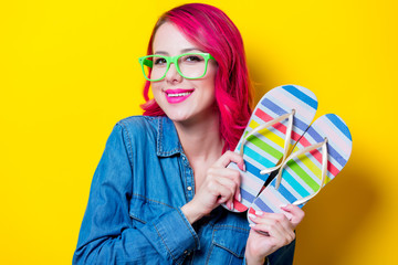 Young pink hair girl in blue shirt and green glasses holding a colored flip flops sandals. Portrait isolated on yellow background