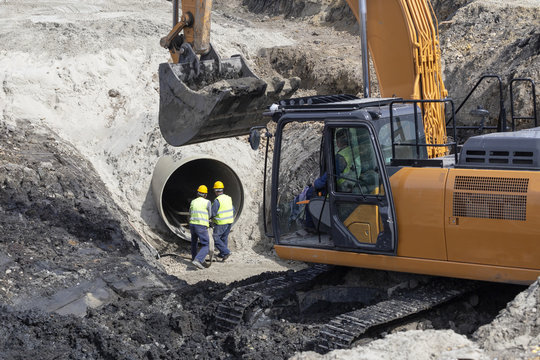 Excavator and workers making trench bed for new pipeline