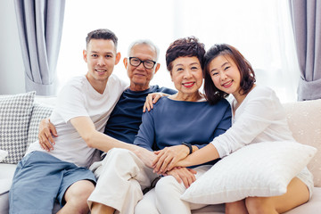 Asian family with adult children and senior parents relaxing on a sofa at home together