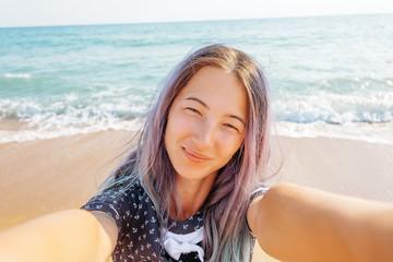 Smiling woman taking selfie on beach.