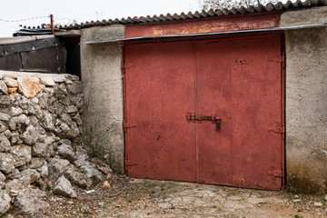Closed red garage door on a cloudy day in Croatia
