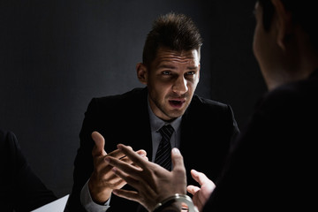 Criminal man being interviewed in interrogation room after committed a crime
