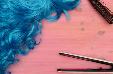 Blue long hair (wig), hair straightener and comb on purple wooden desk table background.