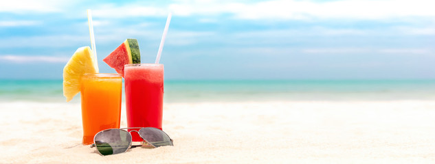 Colorful refreshing cold tropical fruit juice drinks in summer beach banner background