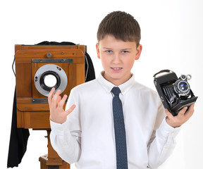 The young emotional photographer with the camera in a hand on the white isolated background.