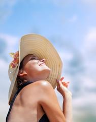 Woman in big straw hat in sun shine