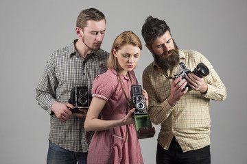 Men in checkered clothes, retro style. Vintage photography concept. Company of busy photographers with old cameras, filming, working. Men, woman on interested faces looks at camera on grey background.