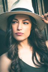 Beautiful young latino woman with panama hat portrait outdoor in the city