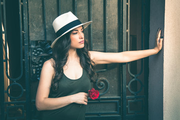 Beautiful young latino woman with panama hat portrait and rose in hand outdoor in the city