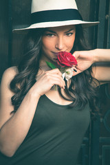 smiling beautiful young latino woman with panama hat portrait and rose  outdoor in the city