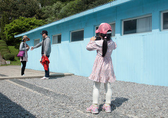 A girl takes a picture of her parents mimicking a handshake between North Korean leader Kim Jong Un and South Korean President Moon Jae-in at the summit in late April, at the replica of the truce village of Panmunjom at a movie studio in Namyangju