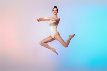 slim gymnast in beige swimsuit