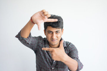 Portrait of smiling Indian man showing frame gesture. Man wearing checked shirt making focus sign. Photographing concept