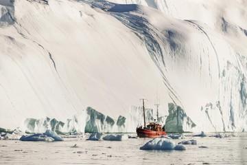 Ship in front of gigantic iceberg