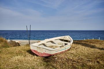Tipica barca in legno messa a secco sulle riva del mar Ionio in Sicilia