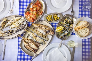 Covered table with delicious clams served on silverware, white wine, tomato salad, bread and olives from above, Portugal, Europe