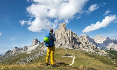 Hiker looking down to Passo Giau, at the back La Gusela, Averau and Tofane, Dolomites, South Tyrol, Trentino-Alto Adige, Italy, Europe