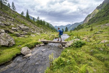 Hiker on a bridge over the Steinriesenbach, hiking trail to the Gollinghutte, Schladminger Hohenweg, Schladminger Tauern, Schladming, Styria, Austria, Europe
