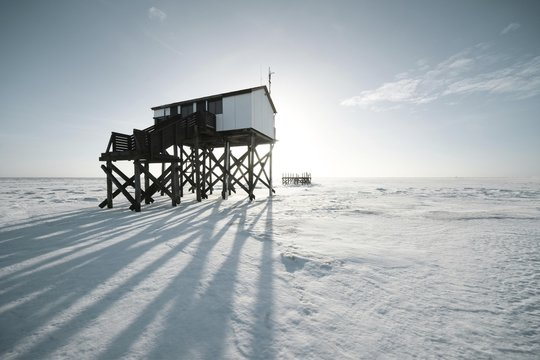 Pile dwelling in winter on a snow-covered beach, Sankt Peter-Ording, Schleswig-Holstein, Germany, Europe