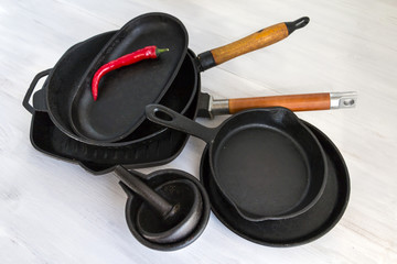 Cast iron cookware, pans, pots on white wooden table.