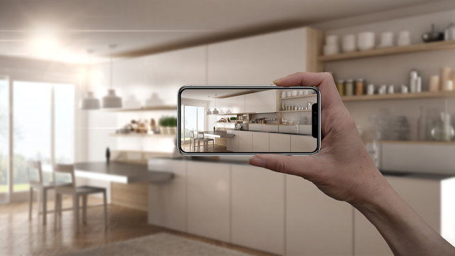 Hand holding smart phone, AR application, simulate furniture and interior design products in real home, architect designer concept, blur background, modern kitchen