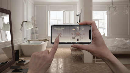 Remote home control system on a digital smart phone tablet. Device with app icons. Interior of minimalist white bathroom in the background, architecture design.
