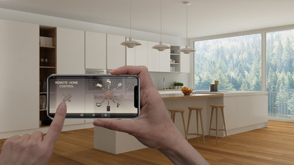 Remote home control system on a digital smart phone tablet. Device with app icons. Interior of minimalist white kitchen in the background, architecture design.
