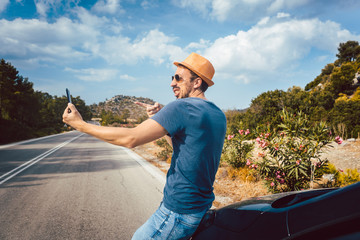 Tourist man making silly selfie photos in his vacation using phone