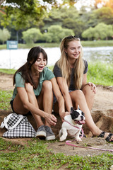 Girlfriends and puppy in park, smiling