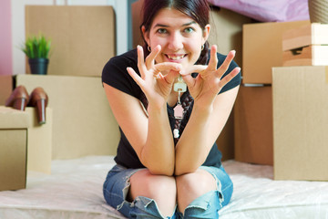 Photo of young brunette with keys from apartment in apartment