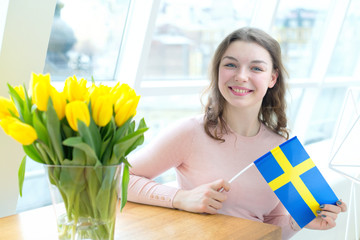 Young woman with the flag of Sweden. A  female student in a bright room near a bouquet of yellow tulips.