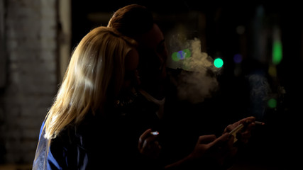 Young couple smoking cigarettes and viewing photos on smartphone together