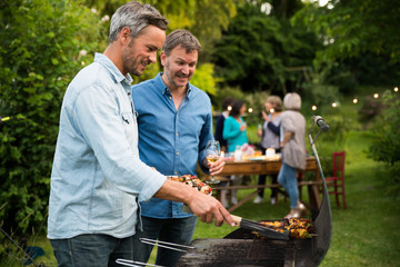 in a summer evening,  two men  in their forties prepares a barbecue for  friends gathered around a table in the garden