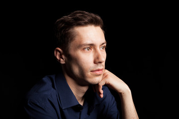 Portrait with fashion lighting of young man on black background